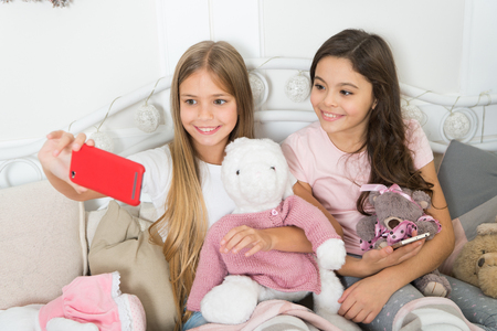 Taking Christmas and New Year selfie with smartphone. Little girls use phone in bed. Merry Christmas and Happy New Year greetings. Happy little children with mobile phone. Self photo.