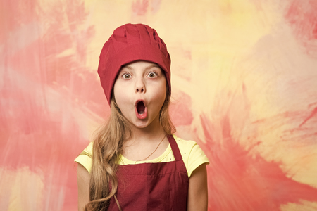 Girl cook with open mouth and surprised face. Child and happy childhood. Career, uniform, dream, occupation and profession concept. Kid in chef hat and apron on colorful wall. Cooking and playing. Standard-Bild