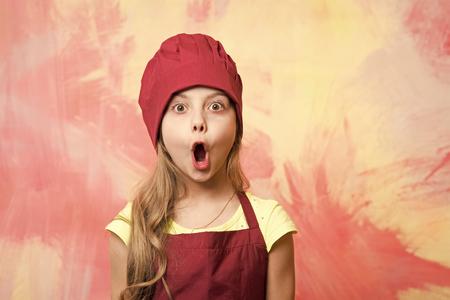 Mädchenkoch mit offenem Mund und überraschtem Gesicht. Kind und glückliche Kindheit. Karriere, Uniform, Traum, Beruf und Berufskonzept. Kind in Kochmütze und Schürze an bunter Wand. Kochen und spielen. Standard-Bild