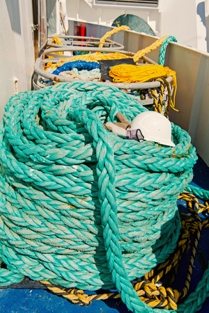 Nautical ropes on ship deck background in Philipsburg, Sint Maarten on sunny day . Rolls of green strings of long twisted threads. Sea voyage and travelling. Yachting and boating concept