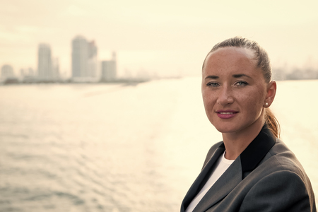 Business woman with freckled face in jacket posing at sea or ocean on blurred grey skyline. Entrepreneurship and prospect concept