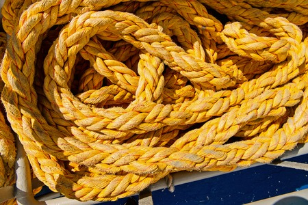 Yellow strings of long twisted threads on sunny day background in Philipsburg, Sint Maarten. Nautical ropes on ship deck. Sea voyage and travelling. Yachting and boating concept