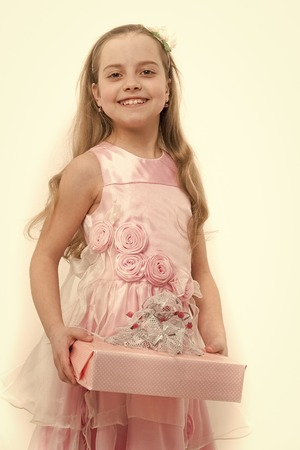 Boxing day concept. Child smile with gift box isolated on white. Girl in pink dress with long blond hair. Holiday present and surprise. Birthday, anniversary celebration.