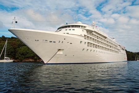 statek wycieczkowy. Duży luksusowy biały liniowiec wycieczkowy na wodzie morskiej i pochmurnym tle nieba w Fowey