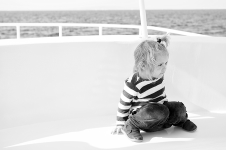 Kid friendly features. Family vacation cruise ship all inclusive tour. Kid boy toddler travelling sea cruise. Child in striped shirt looks like young sailor. Child enjoy vacation on cruise ship. 免版税图像