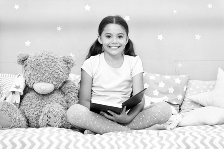 Read fairytale before go to bed. Girl child sit bed with teddy bear read book. Kid prepare to go to bed. Pleasant time in cozy bedroom. Girl kid long hair cute pajamas relax and read book to bear toy. Reklamní fotografie