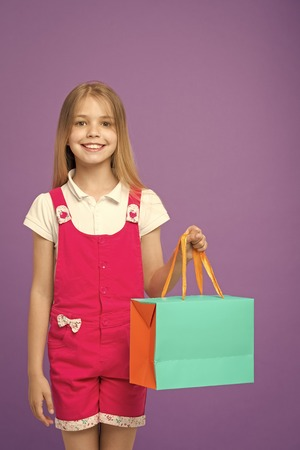 Little child with shopping bag on violet background. Happy girl smile with paper bag. Kid shopper in fashion jumpsuit. Holidays and celebration. Satisfied with her shopping. sale and black friday. Stock Photo