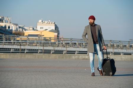 Hipster ready enjoy travel. Carry travel bag. Man bearded hipster travel with luggage bag on wheels. Traveler with suitcase arrive airport railway station urban background. Moving to new city alone.
