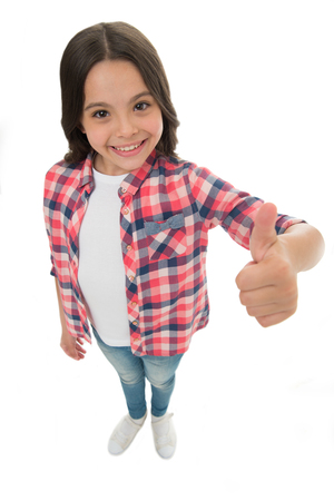 I like it. Kid girl long curly hair posing confidently. Girl smiling face feels confident. Child confidently showing thumbs up. Upbringing confidence concept. Feel so confident with parental support. Imagens