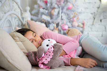 delivery christmas gift. little child girl with xmas present. happy new year. happy little girl celebrate winter holiday. christmas time. morning before Xmas. sleeping and dreaming. Christmas is here.