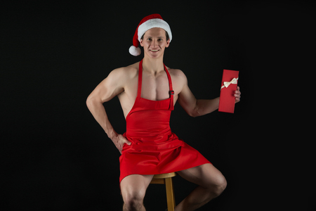 I have gift for you. Macho muscular torso posing with gift box. Santa claus attractive chef. Sexy athletic macho muscular chest in santa claus hat. Athlete muscular man wear santa hat and apron.