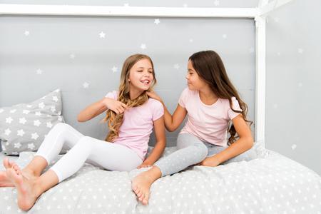 Les enfants se détendent et s'amusent en soirée. Loisirs des soeurs. Les filles en pyjama mignon passent du temps ensemble dans la chambre. Les sœurs communiquent tout en se relaxant dans la chambre. Du temps en famille. Communication entre sœurs.