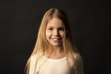 Kid model smiling with long healthy hair. Girl with smile on cute face on dark background. Beauty, look, hairstyle. Happy child, childhood concept. Youth, skincare, health. Stock Photo