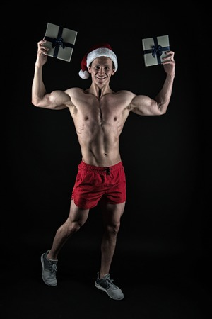 Happy winter holidays. Red. Present for Xmas. New year party. Santa claus man. Christmas shopping. Sexy muscular man in santa hat. I am the best. New year new goals.