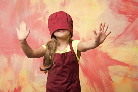 Girl in chef hat on face. Kid cook walking by touch on colorful wall. Cooking and playing concept. Child and childhood.