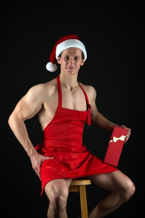 Present for Xmas. Christmas shopping. New year party. Santa claus man. Sexy muscular man in santa hat. Happy winter holidays. Red. Let me be your santa. New year new me. Enjoying New Year party. Stock Photo