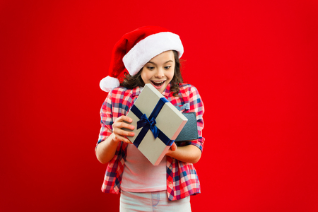 Happy winter holidays. Its for me. Small girl. Present for Xmas. Childhood. Christmas shopping. Little girl child in santa red hat. New year party. Santa claus kid. Christmas time.