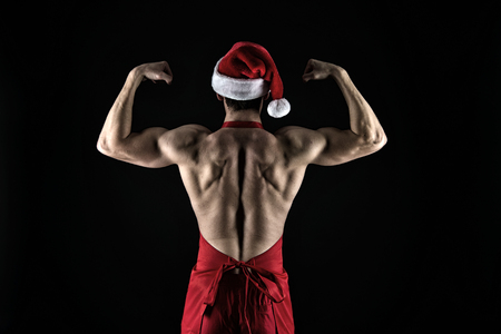 Sexy muscular man in santa hat. Present for Xmas. New year party. Santa claus man. Happy winter holidays. Red. Christmas shopping. I am strong. Christmas is here. New 2019 Year is coming. Stock Photo