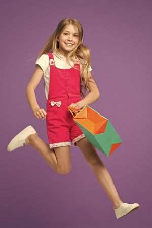 Happy girl jump with shopping bag on violet background. Little child smile with paper bag. Kid shopper in fashion jumpsuit. Holiday preparation and celebration. Shopping and black friday. Stock Photo