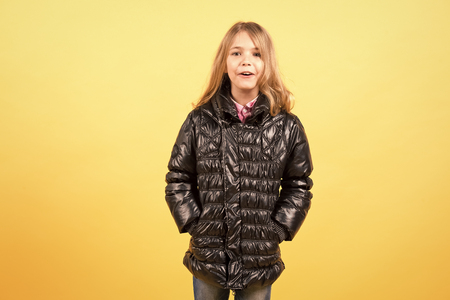 Girl with long blond hair and surprised face, pose with hands in pockets of black jacket on orange background. Fashion, beauty, look, hairdresser concept, copy space