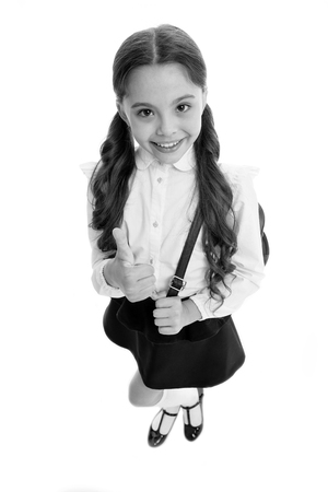 Highly recommend. Schoolgirl shows thumb up gesture, isolated white background. Girl happy smiling recommendation. Child pupil school uniform highly recommend with thumb up gesture. Make right choice. Banco de Imagens