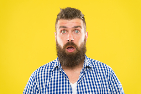 Guy surprised face expression. Hipster with beard and mustache emotional surprised expression. Rustic surprised macho. Surprising news. Man bearded hipster wondering face yellow background close up.