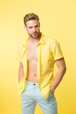 Want to see torso. It is hot here. I will show you my body. Man handsome bearded guy undressing yellow background. Guy confident attractive macho feels while unbuttoning shirt.