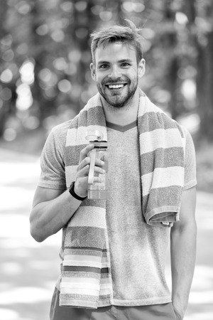 Man with athletic appearance holds bottle with water. Sport and healthy lifestyle concept. Man athlete in sporty clothes training outdoor. Athlete drink water after training at stadium on sunny day. Stockfoto