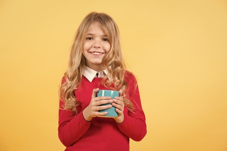 Girl with long blond hair in red sweater hold mug. Health and healthy drink. Child smile with blue cup on orange background. Tea or coffee break. Thirst, dehydration concept. Banco de Imagens - 120363021