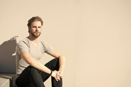 Man in tshirt relax on grey wall, fashion. Macho with bearded face, blond hair on sunny day. Fashion, style concept. Skincare, beauty, grooming, copy space 免版税图像