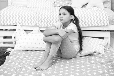 Sad concept. Sad little girl. Sad child sit on bed. Sad kid in bedroom at home. I want to play. Imagens