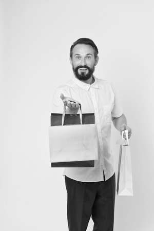 Offer bonus for client good idea. Man mature bearded cheerful face holds shopping bags. Man got unexpectable gifts. Guy surprised by gift yellow background. Presents make our lives more interesting.