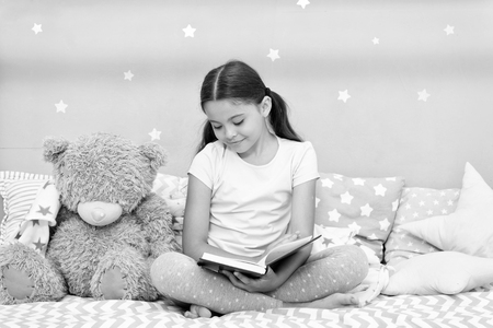 Read before sleep. Girl child sit bed with teddy bear read book. Kid prepare to go to bed. Pleasant time in cozy bedroom. Girl kid long hair cute pajamas relax and read book to bear toy. Reklamní fotografie
