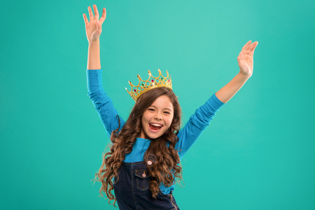 Feels like queen. Kid wear golden crown symbol of princess. Lady little princess. Girl cute baby wear crown while stand blue background. Childhood concept. Every girl dreaming to become princess.