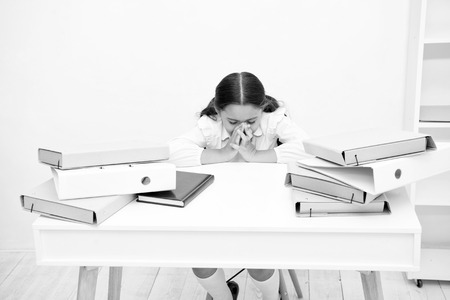 So nervous about coming test. Girl child reads book while sit table white background. Schoolgirl studying prepare for test or exam. Kid girl school uniform nervous about coming test check knowledge.