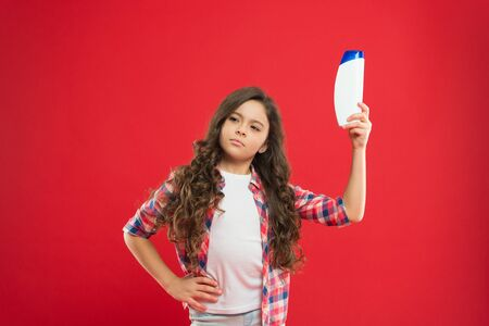 Girl long curly hair hold shampoo bottle. Little child on red background. Hairdresser salon concept. Shampoo for curly hair. Conditioner balm nourish damaged hair. Best choice. Curly hair remedies.