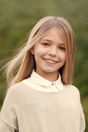 Child in grey sweater on idyllic autumn day. Girl with blond long hair smile on natural landscape. Happy childhood concept. Beauty, youth, growth. Kid fashion and style. Zdjęcie Seryjne