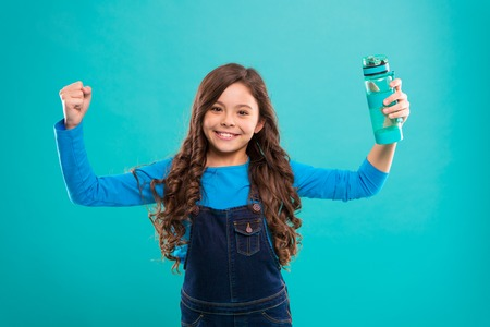 Healthy and hydrated. Girl cares about health and water balance. Girl cheerful hold water bottle blue background. Kid girl long hair has water bottle. Water balance concept. Strong and healthy child.
