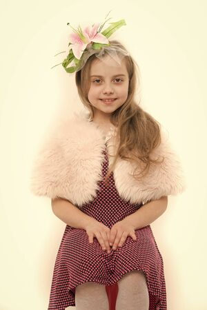 Fashion and beauty salon. Child wear fur cape and dress. Girl smile with flower in long blond hair. Retro, vintage style. Holiday, birthday, winter celebration concept.