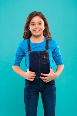 Pure beauty. Little girl with long hair. Kid happy cute face with adorable curly hair stand over blue background. Beauty tips for tidy hair. Kid girl long healthy shiny hair wear casual clothes.