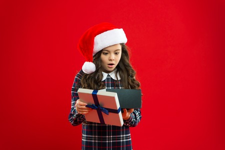 Wow. Little girl child in santa red hat. Christmas shopping. Happy winter holidays. Small surprised girl. Present for Xmas. Childhood. New year party. Santa claus kid. What.