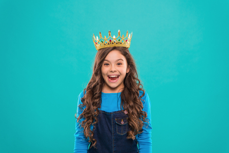 Beauty contest model. Kid wear golden crown symbol of princess. Every girl dreaming to become princess. Lady little princess. Girl cute baby wear crown while stand blue background. Childhood concept. Banco de Imagens