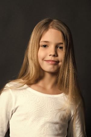 Juventud, cuidado de la piel, salud. Chica con sonrisa en cara linda sobre fondo oscuro. Belleza, mirada, peinado. Niño feliz, concepto de infancia. Modelo de niño sonriendo con cabello largo sano. Foto de archivo