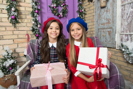 Santa visits us only once a year. Cute children with new year presents. Merry Christmas and Happy New Year. Happy little girls hold gift boxes. Festive preparation for Christmas and New Year at home. Stock Photo