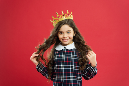 Every girl dreaming become princess. Lady little princess. Girl wear crown red background. Spoiled child concept. Egocentric princess. World spinning around me. Kid wear golden crown symbol princess. Stock Photo
