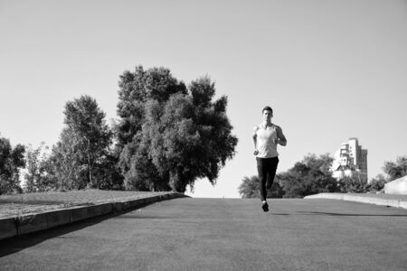 runner on sunny road. man runner training outdoor. runner athlete workout. confident runner Zdjęcie Seryjne