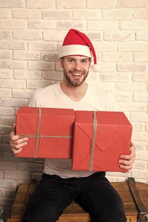 Macho smile in christmas hat hold wrapped presents. Man santa with boxes on white brick wall. Happy boxing day. Gift giving and exchange concept. Holidays preparation and celebration.