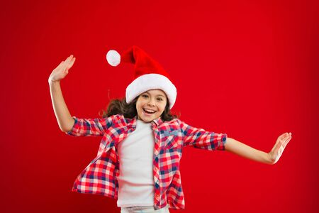 Lets do this. Happy winter holidays. Small girl. Present for Xmas. Childhood. New year party. Santa claus kid. Christmas shopping. Little girl child in santa red hat. Real feelings. Zdjęcie Seryjne