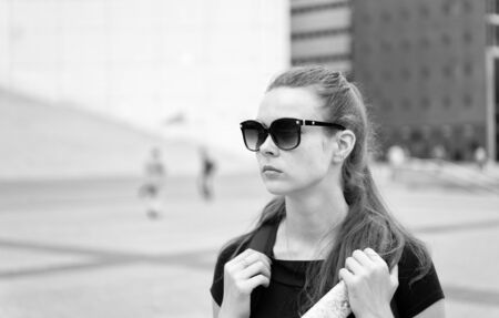 Girl tourist sunglasses enjoy view Paris square city center. Woman stand in front of urban architecture copy space. Must visit place. Guide for tourists to explore Paris. Backpacker exploring city. 写真素材