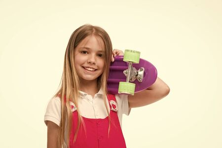 Child skater smiling with longboard. Born to be a skater girl. Small girl smile with skate board isolated on white. Skateboard kid with long hair. Sport activity and energy. Childhood and active game. 스톡 콘텐츠